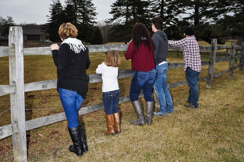 Family Standing by a Wood Fence Family Farm Field Standing Wood Fence Full Length Leisure Activity Lifestyles Men Nature Outdoors People Real People Togetherness Women Young Adult Young Women