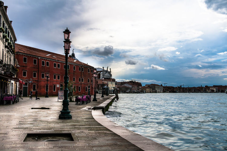 Promenade by grand canal against sky