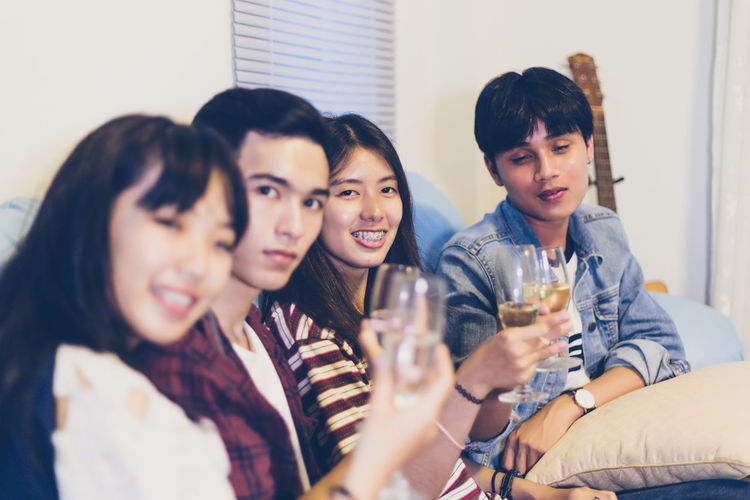 Portrait Of Friends Enjoying Champagne During Celebration At Home