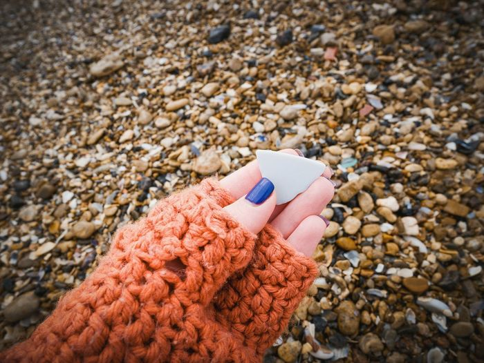 Close-Up Of Woman Hand Holding Ceramics At Beach