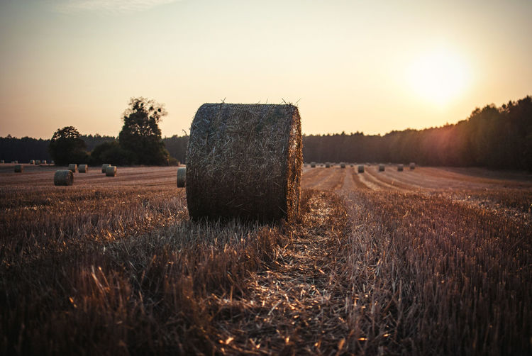 Hay Bales At Field Against Sky During Sunset