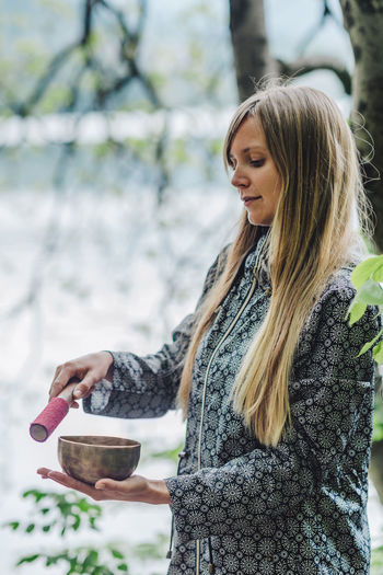Side View Of Young Woman Holding Bowl While Standing In Park
