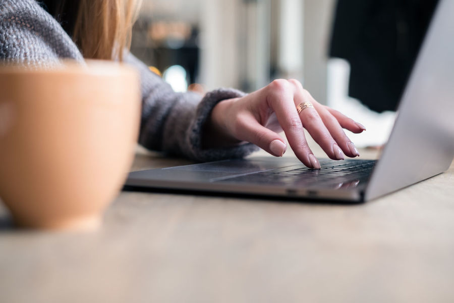 woman typing on laptop Laptop Wireless Technology Using Laptop Technology One Person Computer Communication Connection Human Hand Indoors  Human Body Part Selective Focus Typing Real People Furniture Table Hand Women Surfing The Net Using Technology Cup Of Coffee Freelance Life Lifestyle