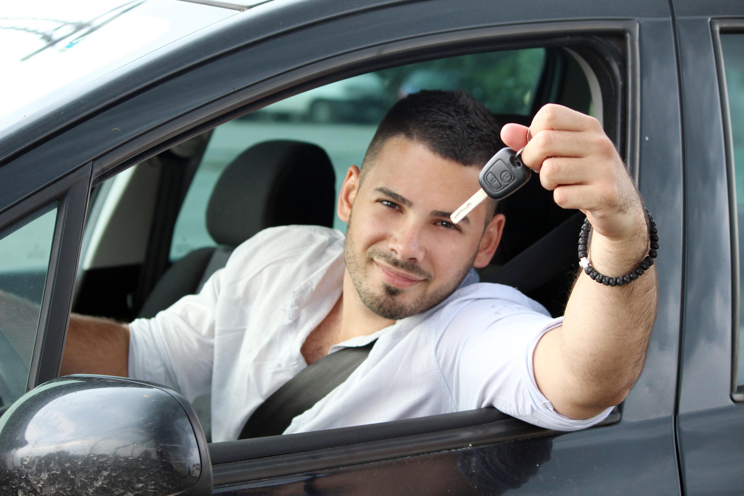 PORTRAIT OF MAN SITTING ON CAR