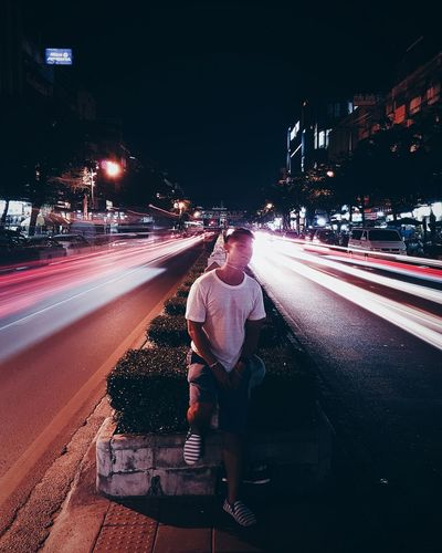 Young Man Looking At Light Trails On Road In City