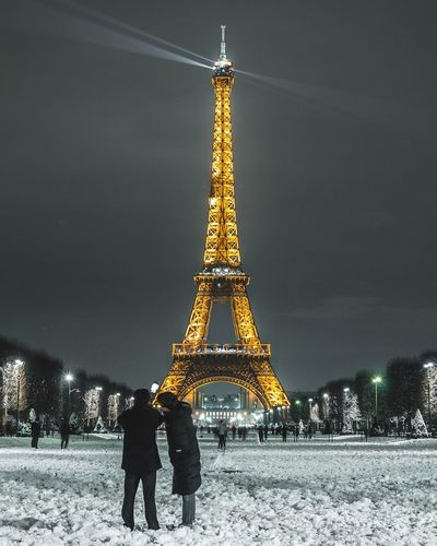 Tourists stuff Tour Eiffel Paris Snow Tower Travel Destinations Architecture Tourism Built Structure Tall - High Travel City Life Real People City Illuminated Cold Temperature Leisure Activity Night Outdoors