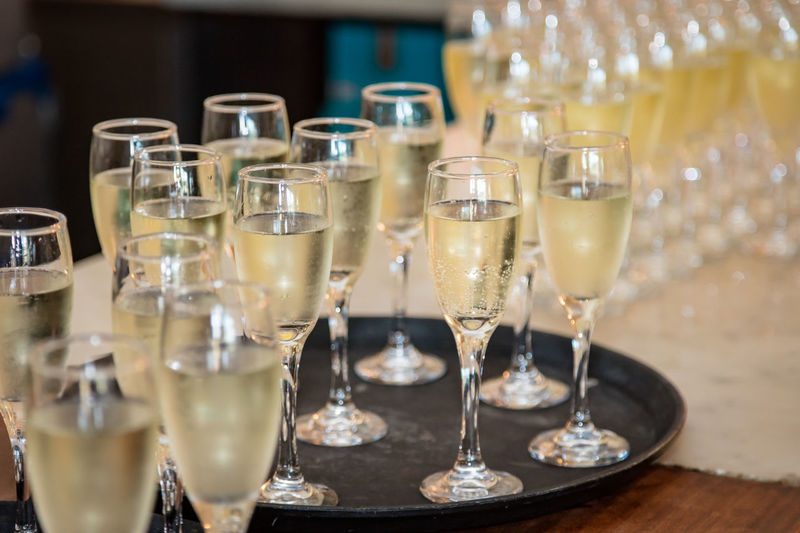 Close-up of champagne flutes in tray on table