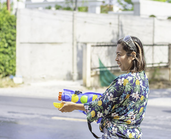 Young woman playing with squirt gun on road