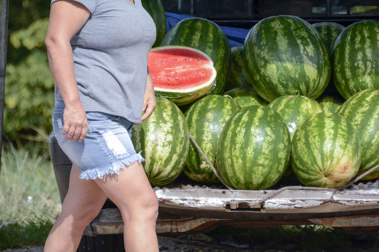 Midsection of woman walking by watermelons in trunk