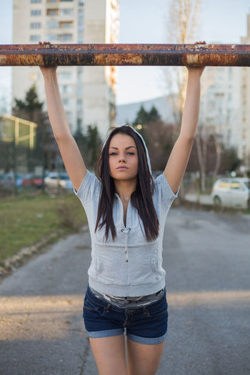 Young Woman Exercising Against Building
