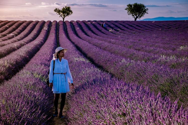 Full length of woman standing on flowering plants
