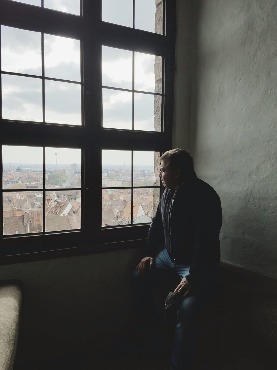 Man Looking City Through Window At Home