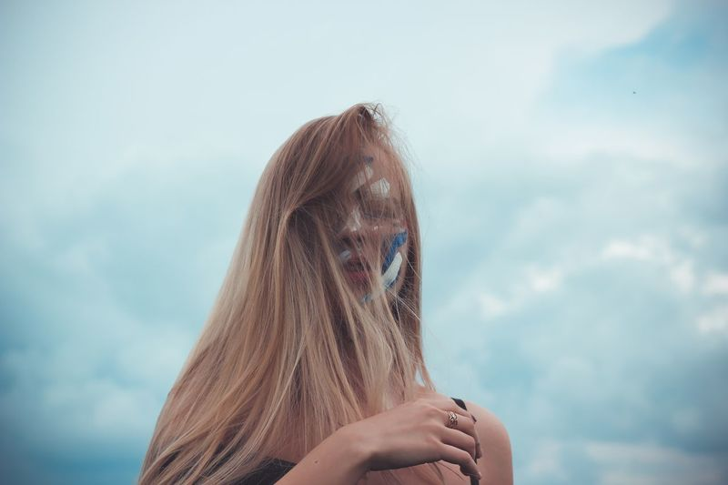 Young Woman With Blond Messy Hair Standing Against Sky