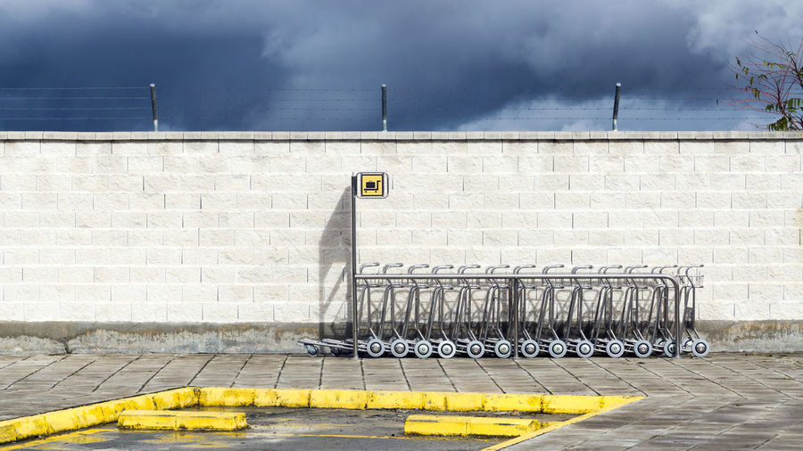 airport still life Wall Day No People Yellow Brick Wall Cloud - Sky Outdoors Sky Brick Pavement Bus Stop Granada, Spain Airport Luggage Trolleys Sign Fence Grx Bricks Cart Holiday Moments
