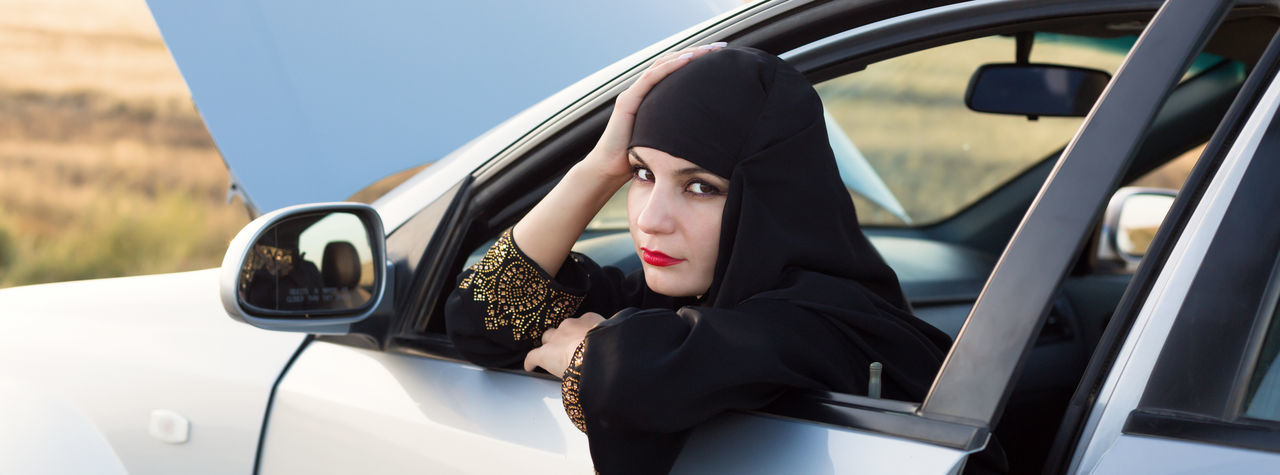 Portrait of woman wearing hijab sitting in car