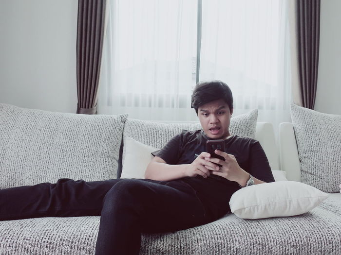 Shocked young man using smart phone while relaxing on sofa at home