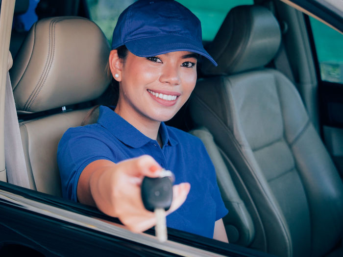 Portrait of smiling woman giving key while sitting in car