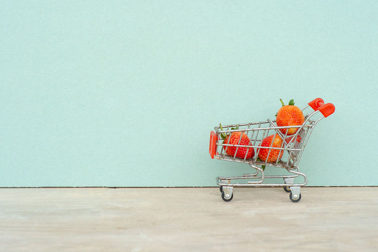 Closeup strawberries in the shopping trolley. Cart carrying the strawberry with the isolated background Shopping Cart Studio Shot Colored Background Wheel Supermarket Delivery Shopping Fruit