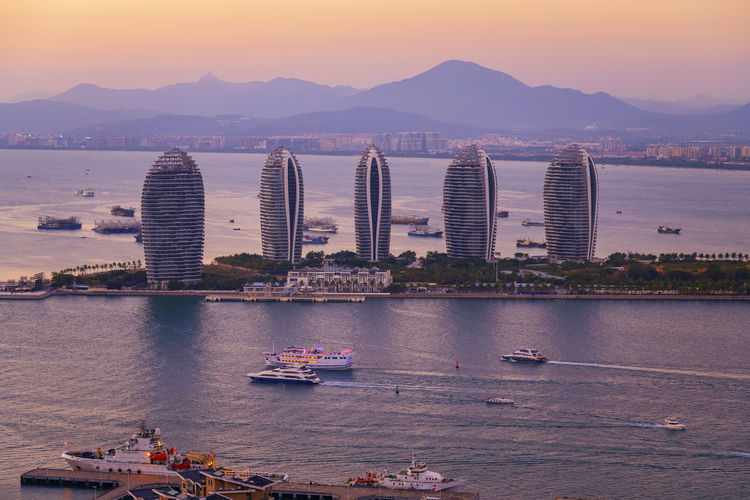Aerial view of Sanya city and Dadonghai bay from Luhuitou Park in Hainan province, China Travel Travel Destinations Travel Photography Built Structure Water Transportation Architecture Sky Sunset Nature Sea Bay Nautical Vessel Architecture Sanya Sanya.China China Cityscape cityscapes Mountain Technology Building Boat