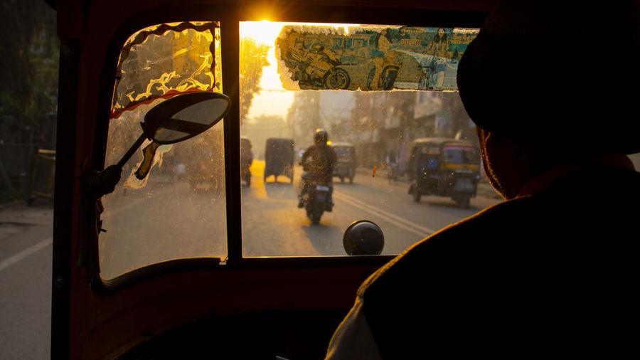 Man driving rickshaw in city during sunset
