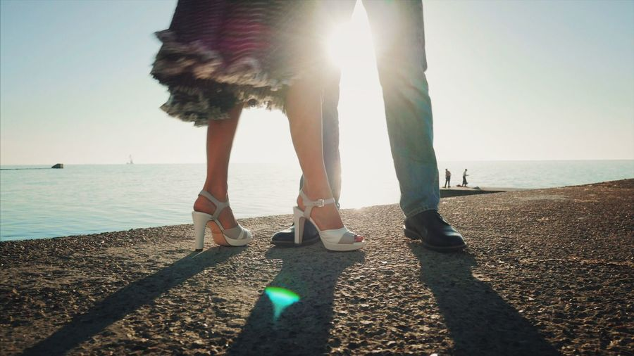 Low Section Sea Sunlight Human Leg Lens Flare Beach Sunbeam Couple Salsa Bachata Dancing Sea And Sky Backgrounds Sun Day Outdoors Sky Standing Shadow Water Nature Real People Women Sand Leisure Activity