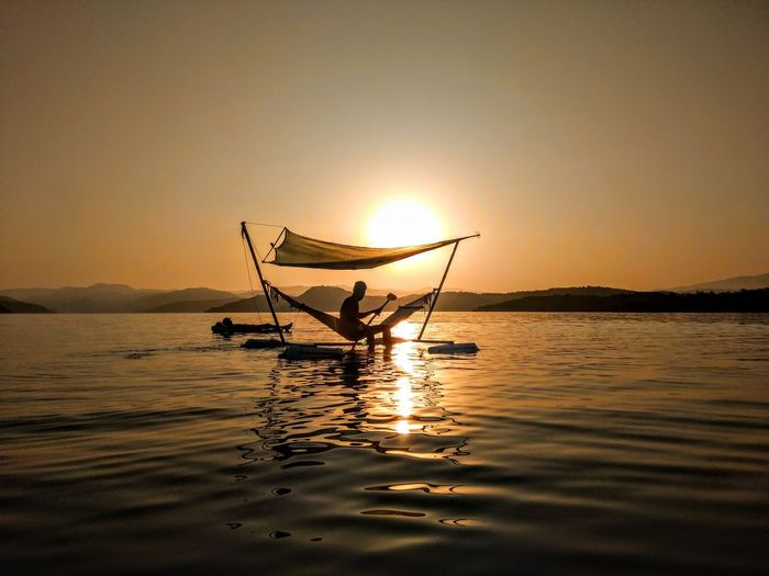 Silhouette man sitting on hammock over sea against clear sky during sunset