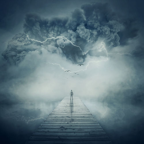 Digital composite image of man standing on pier over sea during storm