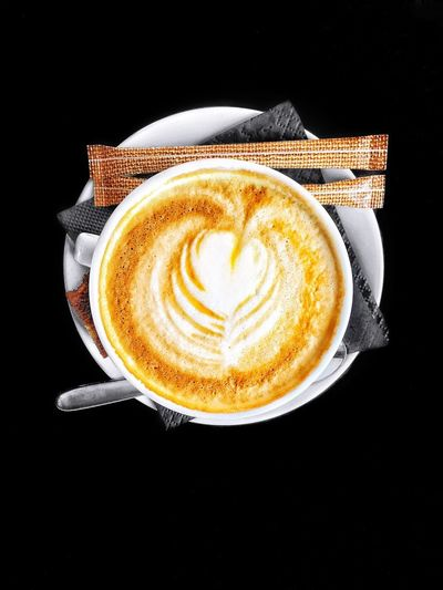 Close-up of cappuccino over black background