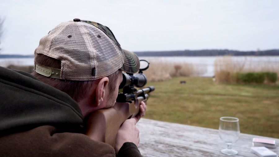 Close-Up Of Man Aiming With Rifle Against Lake