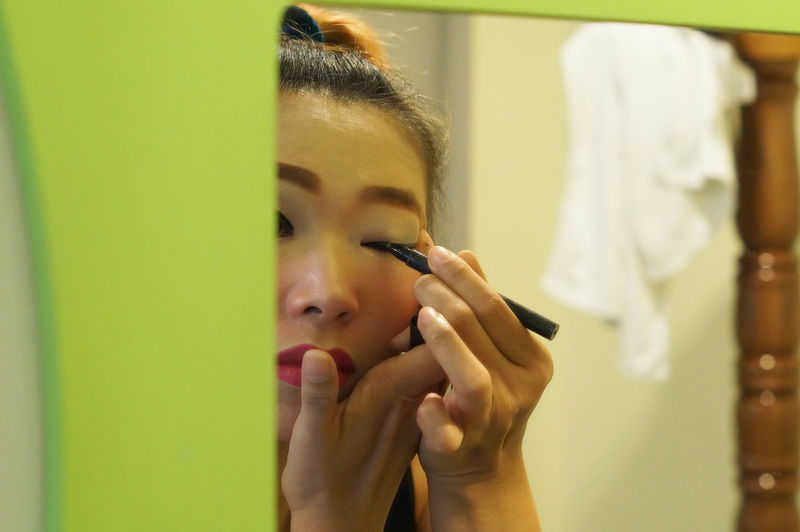 Reflection of woman applying eyeliner in mirror at home
