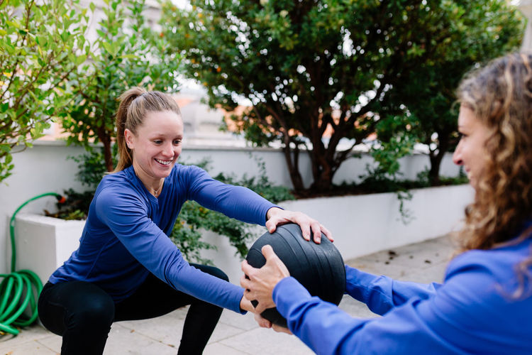 Instructor with woman exercising against plants