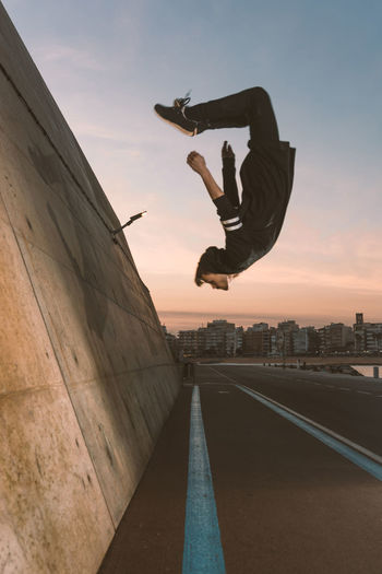 Sky One Person Real People Mid-air Sunset Architecture Full Length Lifestyles City Stunt Balance Men Leisure Activity Jumping Nature Building Exterior Built Structure Skill  Outdoors Human Arm