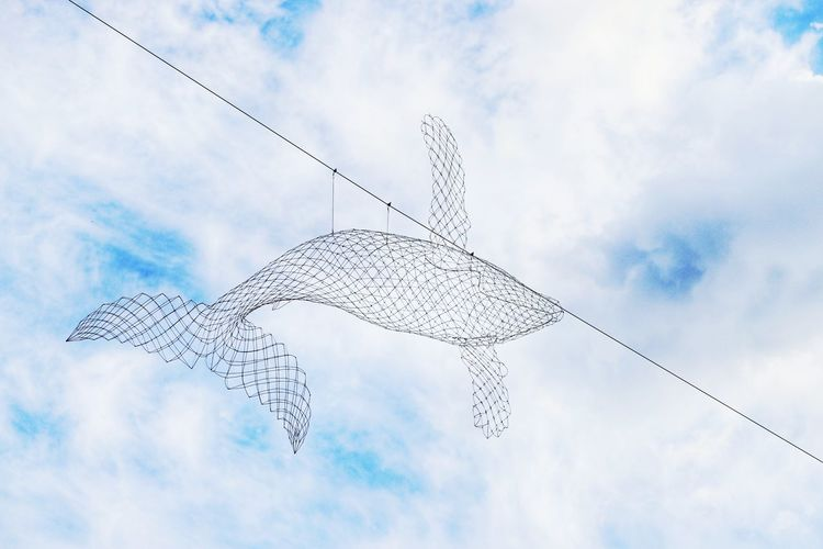 Low angle view of metallic fish decor hanging from cable against sky