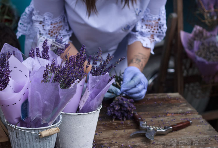 Midsection of woman making bouquet at flower shop