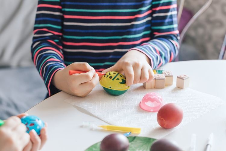 Close-Up Of Siblings Drawing On Easter Eggs At Table