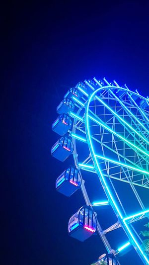 Low angle view of illuminated ferris wheel against clear blue sky