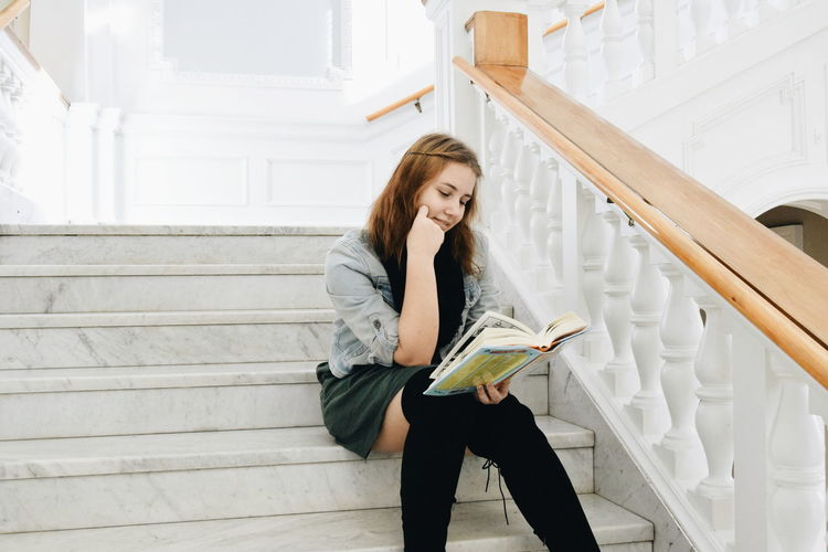 Young Student Reading On Stairs