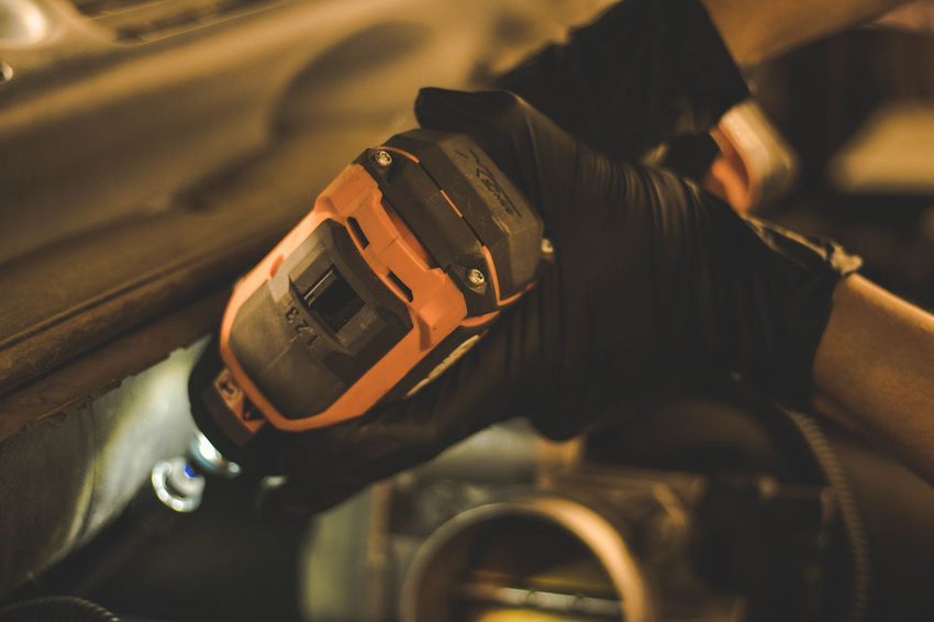 Mechanic working in engine compartment with power tools. Dark Engine Compartment Hands Machine Mechanic Auto Auto Mechanic Automotive Blackandwhite Close-up Engineering Fingers Gloves Maintenance Maintenance Work Orange Color Ratchet Spark Plugs Thumbs Up Tools Water Working Hands Wrist