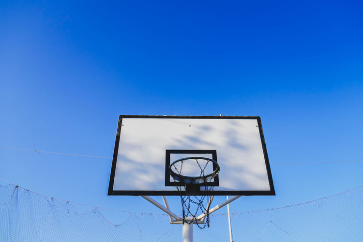 Basketball Basket Basketball Basketball Game Basketball Hoop Blue Cable Day Geometric Shape High Section Information Information Sign Low Angle View No People Outdoors Pole Power Supply Sky White