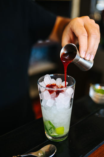 Close-up of hand holding drink served on table