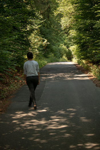 Casual Clothing Day Direction Forest Full Length Growth Lifestyles Nature One Person Outdoors Plant Real People Rear View Road Sunlight The Way Forward Tree Walking