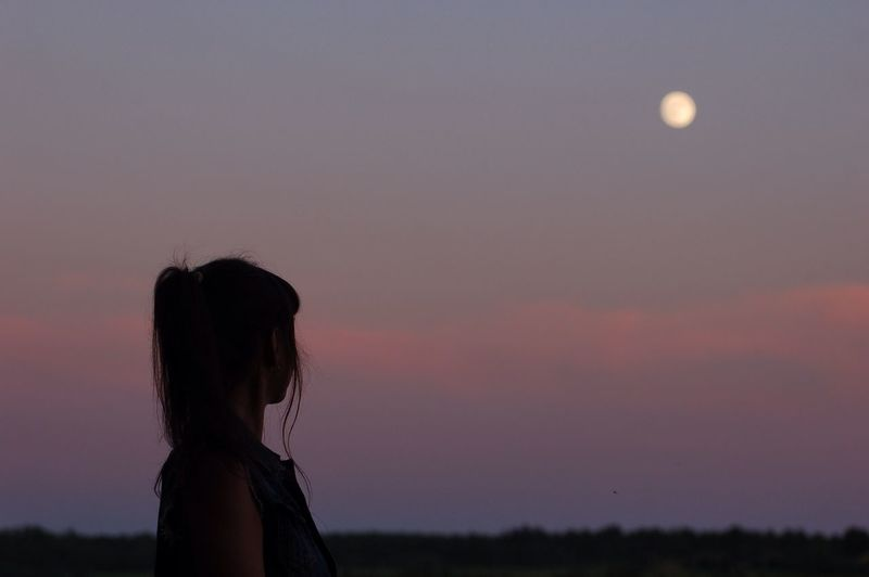 Woman Looking At Moon In Sky During Sunset
