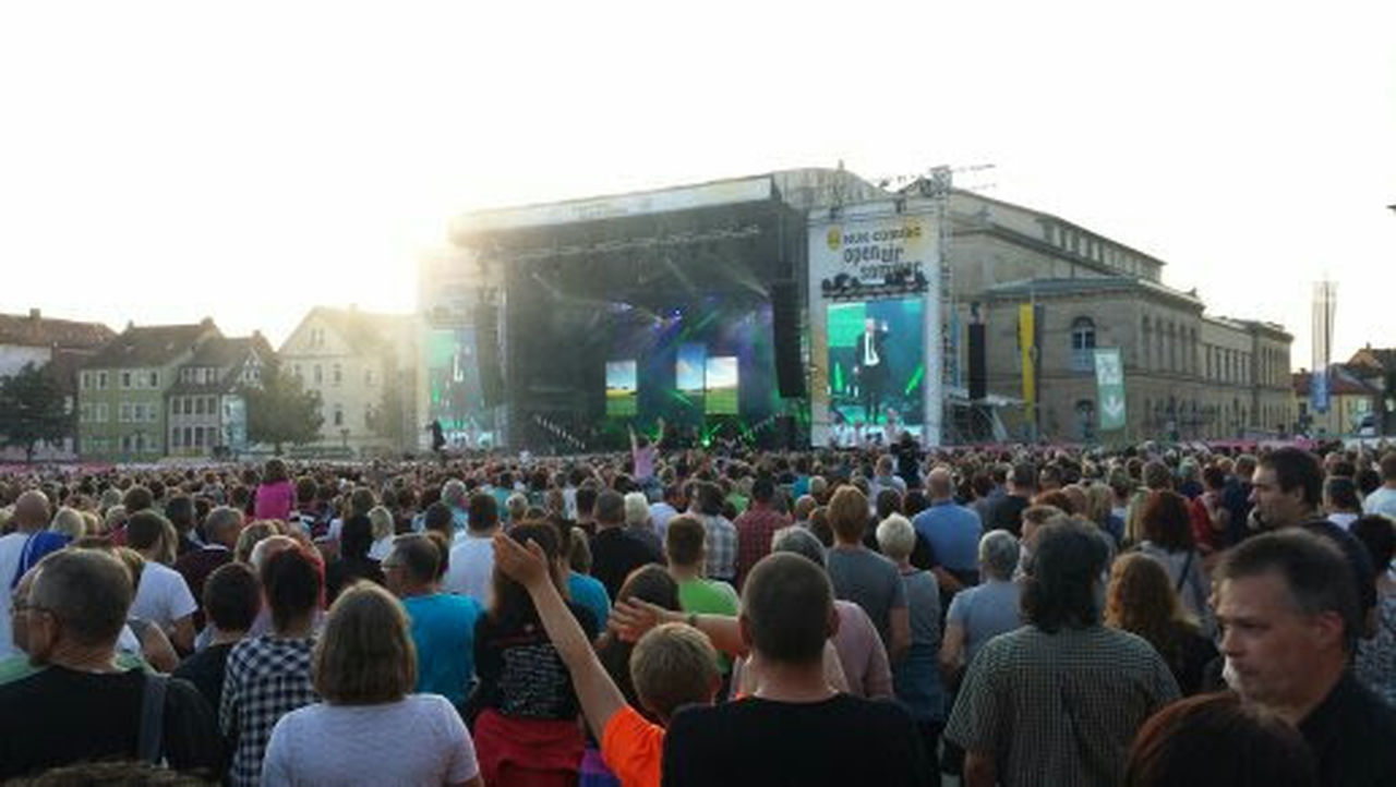large group of people, crowd, music festival, music, arts culture and entertainment, people, stage - performance space, performance, illuminated, live event, adult, audience, adults only, summer, built structure, building exterior, outdoors, architecture, night, popular music concert, young adult, sky, musician
