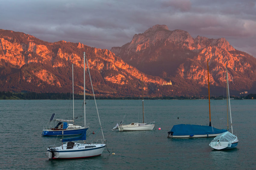 Neuschwanstein Beauty In Nature Boat Cloud - Sky Day Forggensee Mode Of Transport Moored Mountain Mountain Range Nature Nautical Vessel No People Outdoors Rock - Object Scenics Sea Sky Tranquil Scene Tranquility Transportation Water Waterfront