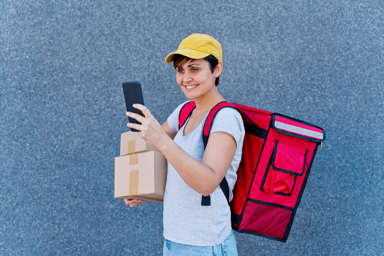 Portrait of smiling young man holding mobile phone
