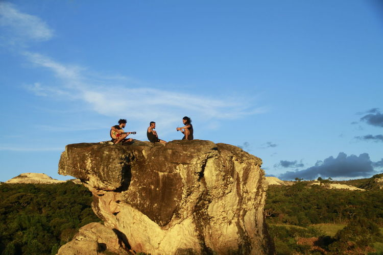 Friends Sitting On Rock Formation Against Sky