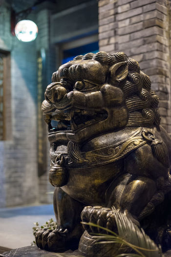 lion Art And Craft Sculpture Representation Creativity Statue Built Structure Belief Human Representation Religion Architecture Building No People Craft Spirituality Focus On Foreground Day Male Likeness Place Of Worship Idol
