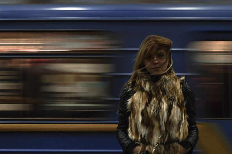 Portrait of young woman standing against train moving in background at station
