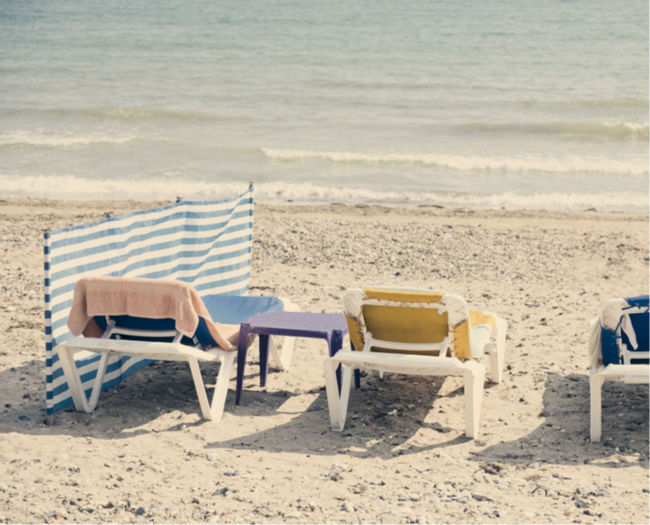 Rear view of lounge chairs on beach