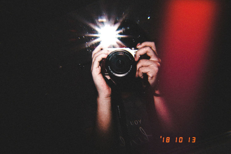 Midsection of woman photographing at night